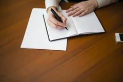 hon skriver pennan på ett block Royaltyfria Foton