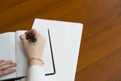 hon skriver pennan på ett block Arkivbild