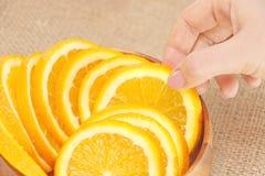 Hon tar en skiva av apelsinen i en träbunke Arkivbilder