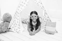 Hon utstrålar förälskelse Lägger det gulliga barnet för flickan i hjärta format glasögon att koppla av i tipi i hennes sovrum Gul arkivbild
