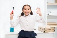Hon vet högert svar Barnflickan bär skolalikformign som står upphetsat framsidauttryck Smarta barnblickar för skolflicka royaltyfri bild