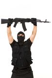 Honcho. Portrait of terrorist in balaclava holding rifle above himself on white background Royalty Free Stock Photography