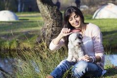 Hond die met haarborstel door jonge vrouw in het park worden verzorgd stock foto's