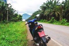 Honda motobike przy drogą though tropikalny las deszczowy Obrazy Royalty Free