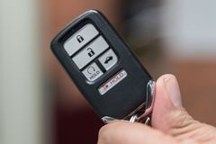 Remote Key FOB for modern car in hand. Honda remote start key FOB keyless entry black in hand isolated blur Royalty Free Stock Images