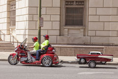 Honda tre person som drar en skottkärra med en släp Royaltyfria Foton