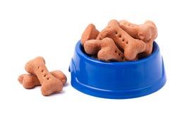 Hondebrokjes in de vorm van beenderen in blauwe plaat, op wit Stock Fotografie