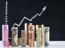 Honderd Amerikaanse dollar en andere munt gerolde rekeningenbankbiljetten, met gestapelde muntstukken Royalty-vrije Stock Afbeeldingen