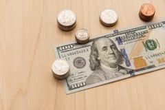 Honderd die dollarsrekening door een stapel muntstukken wordt omringd royalty-vrije stock foto's