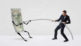 Honderd die dollarsrekening met armen en benen in een lasso door een kleine zakenman worden gevangen Stock Afbeeldingen