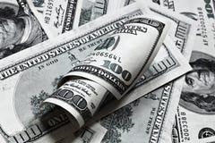 Honderd dollar bankbiljettenachtergrond met broodje Stock Fotografie