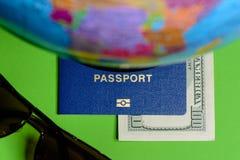 Honderd dollars en een paspoort op een groene achtergrond met een kaart van de bol stock fotografie