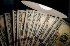 Honderd dollars en een schemerlamp stock afbeeldingen