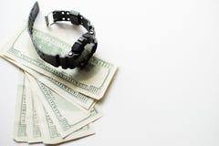 Honderd dollars met modern die polshorloge op witte achtergrond wordt geïsoleerd zwart horloge met geld stock afbeeldingen