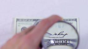 Honderd dollars onder het vergrootglas stock footage