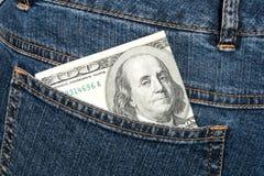 Honderd dollarsbankbiljet in heup-zak van jeans stock afbeelding