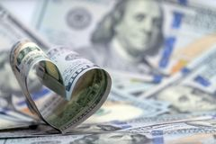 Honderd dollarsbankbiljet van de V.S. in de vorm van een hart De Achtergrond van het geld r stock foto's