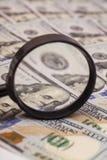 Honderd dollarsbankbiljetten onder vergrootglas Stock Foto