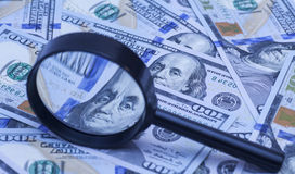 Honderd dollarsbankbiljetten onder vergrootglas Stock Afbeelding