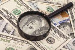 Honderd dollarsbankbiljetten onder vergrootglas Royalty-vrije Stock Foto