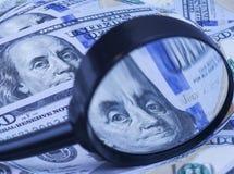 Honderd dollarsbankbiljetten onder vergrootglas Royalty-vrije Stock Afbeelding