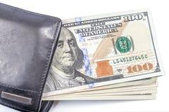 Honderd dollarsbankbiljetten in zwarte leerportefeuille op witte bedelaars Stock Foto's