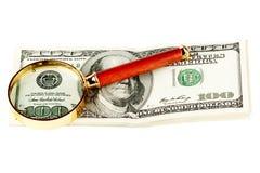 Honderd dollarsrekening onder een vergrootglas Stock Foto's