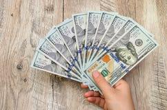 Honderd dollarsrekeningen in de hand van een vrouw op een houten achtergrond royalty-vrije stock afbeeldingen