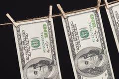 Honderd Dollarsrekeningen die van Drooglijn op Donkere Achtergrond hangen Stock Fotografie