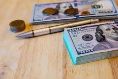 Honderd dollarsrekeningen, Thaise muntstukken en pen op oude houten Stock Foto's