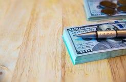 Honderd dollarsrekeningen, Thaise muntstukken en pen op oude houten Stock Foto