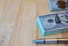 Honderd dollarsrekeningen, Thaise muntstukken en pen op oude houten Stock Fotografie