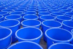 Honderden lege blauwe die wateremmer op de vloer wordt gelegd Stock Afbeeldingen