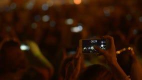Honderden mensen die video's van vuurwerk op hun smartphones op muziekfestival maken stock video