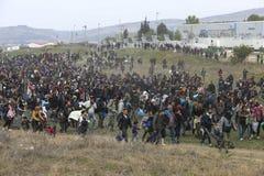 Honderden migranten en vluchtelingen buiten een vluchtelingskamp worden verzameld in Diavata die stock fotografie