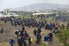 Honderden migranten en vluchtelingen buiten een vluchtelingskamp worden verzameld in Diavata die stock foto's
