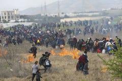 Honderden migranten en vluchtelingen buiten een vluchtelingskamp worden verzameld in Diavata die stock foto
