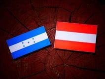Honduras flag with Austrian flag on a tree stump  Stock Images