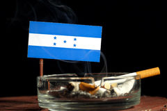 Honduras flag with burning cigarette in ashtray on black. Background stock photography