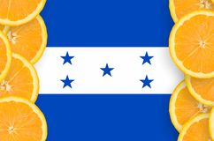 Honduras flag in citrus fruit slices vertical frame. Honduras flag in vertical frame of orange citrus fruit slices. Concept of growing as well as import and stock illustration