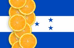 Honduras flag and citrus fruit slices vertical row. Honduras flag and vertical row of orange citrus fruit slices. Concept of growing as well as import and export stock images