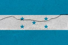 Honduras flag on concrete wall with crack. Patriotic grunge background. National flag of Honduras royalty free stock photos