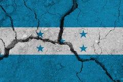 Honduras flag on the cracked earth. National flag of Honduras. Earthquake or drought concept stock image