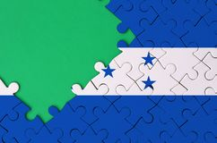 Honduras flag is depicted on a completed jigsaw puzzle with free green copy space on the left side.  stock illustration