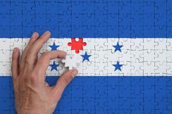 Honduras flag is depicted on a puzzle, which the man`s hand completes to fold.  stock photo