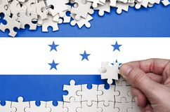 Honduras flag is depicted on a table on which the human hand folds a puzzle of white color.  stock image