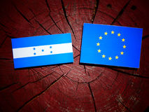 Honduras flag with EU flag on a tree stump isolated. Honduras flag with EU flag on a tree stump Stock Images
