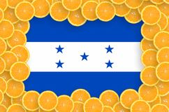Honduras flag in fresh citrus fruit slices frame. Honduras flag in frame of orange citrus fruit slices. Concept of growing as well as import and export of citrus stock images
