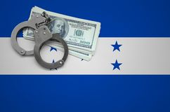 Honduras flag with handcuffs and a bundle of dollars. The concept of breaking the law and thieves crimes.  royalty free stock photography
