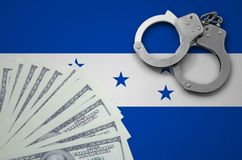 Honduras flag with handcuffs and a bundle of dollars. The concept of illegal banking operations in US currency.  stock photos
